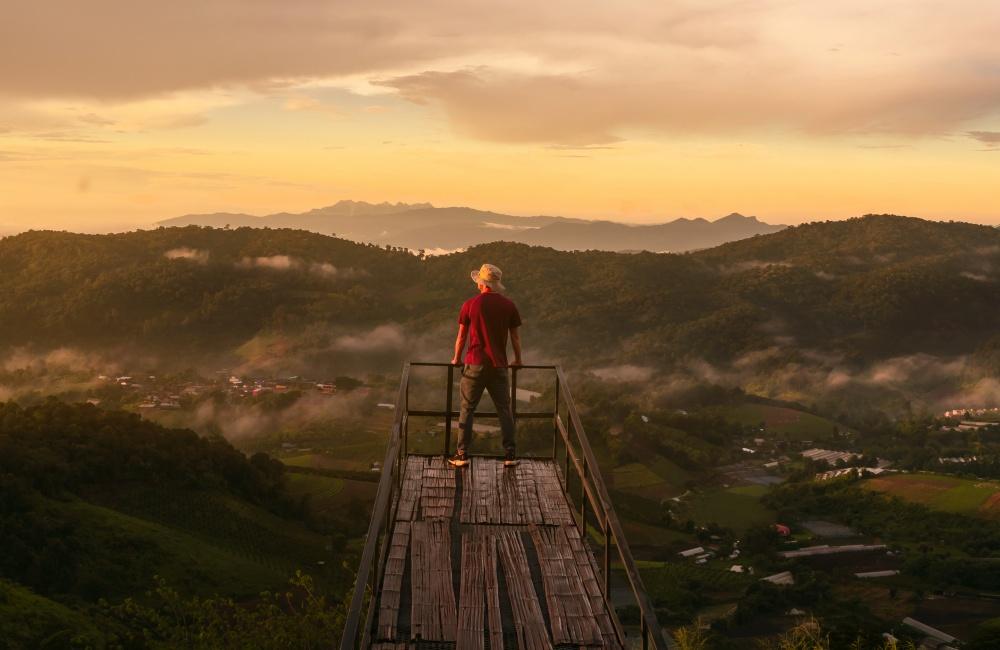 山々と田舎町の絶景を眺める男