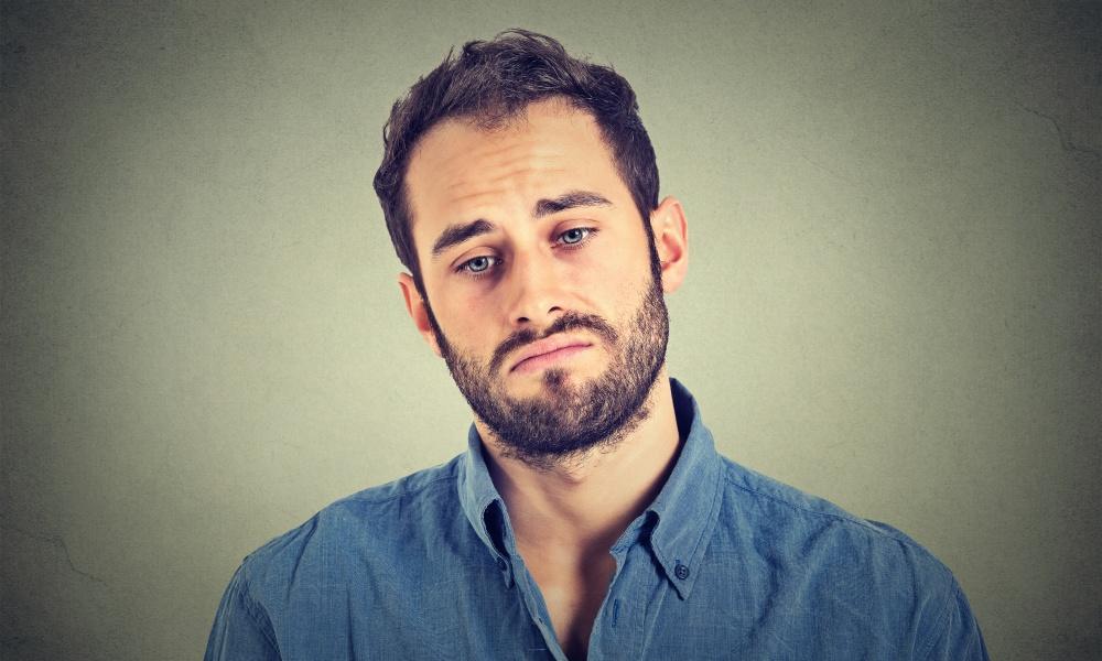 悲しい表情をする男性