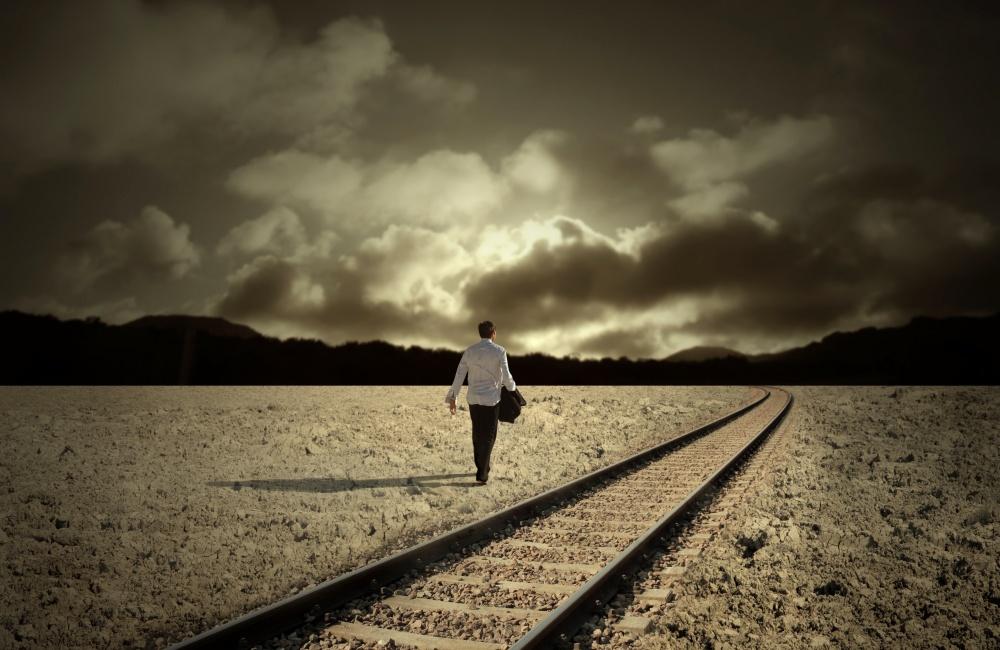 線路の横を歩く男