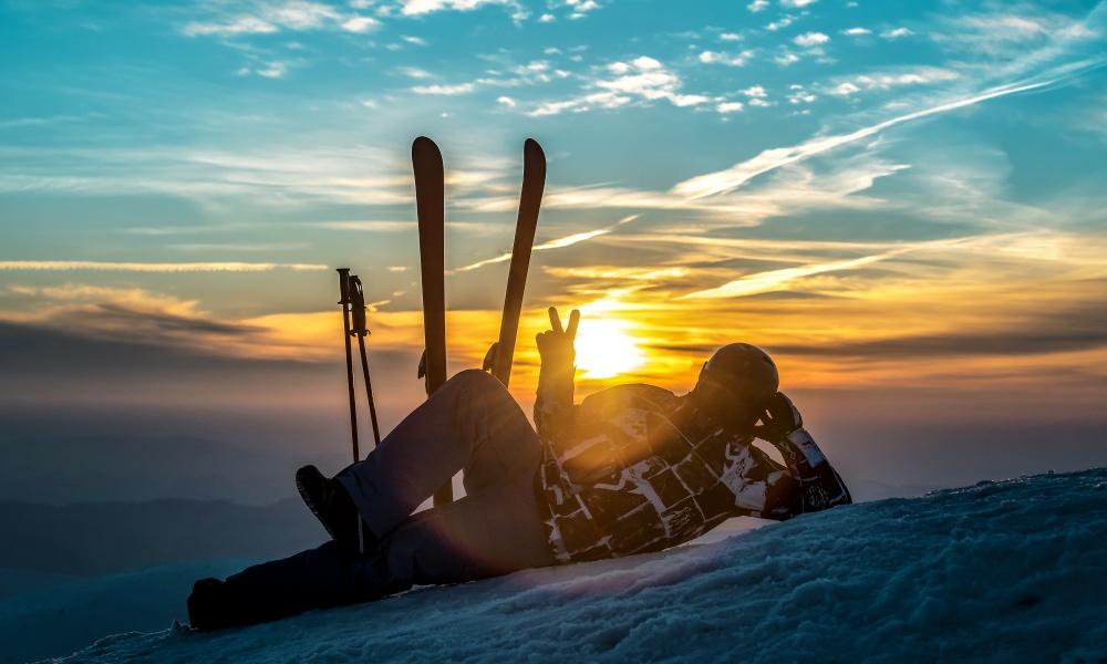 スキー場で夕日に向かってピースするスキーヤー