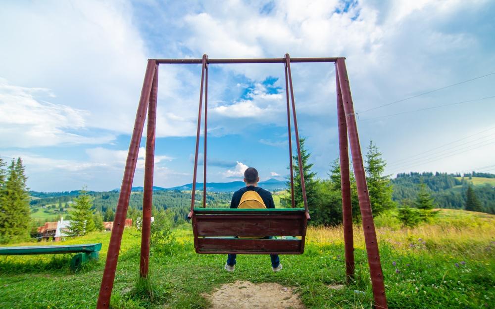 公園のブランコに座る男