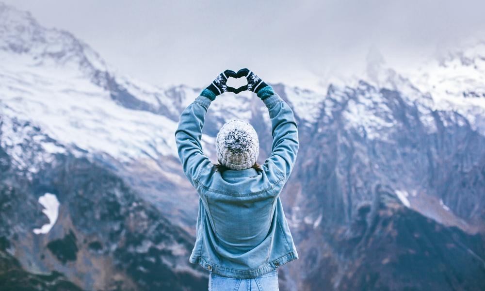 絶景の雪山にハートを送る女性