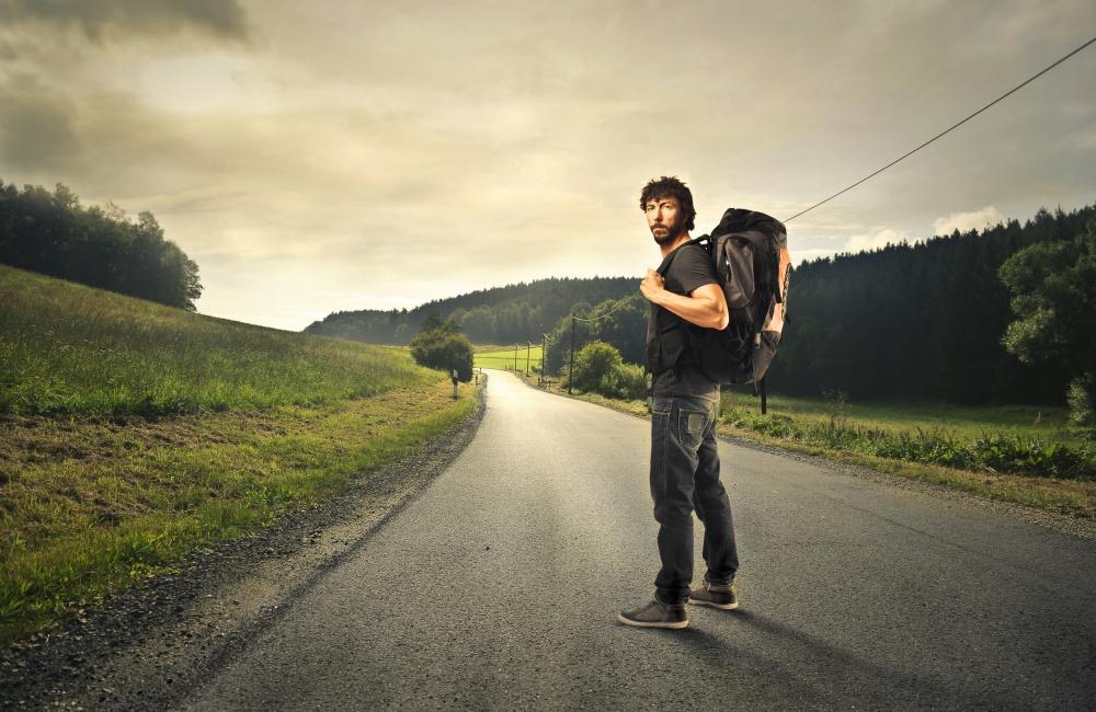 バックパックを背負って旅する男