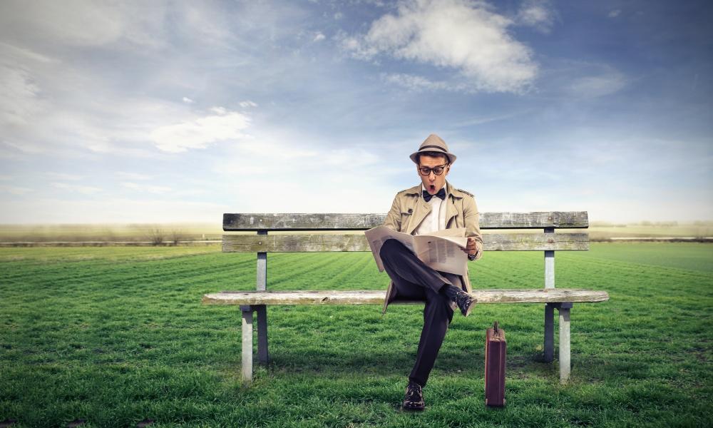 大草原で新聞を読む男